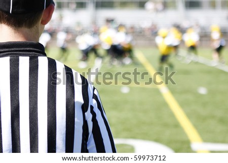 Referee on field during a football game. - stock photo