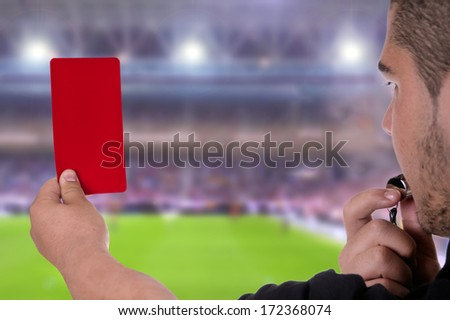 Referee showing the red card in the soccer stadium - stock photo