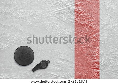 Referee whistle and washer on the hockey rink. Texture, background - stock photo
