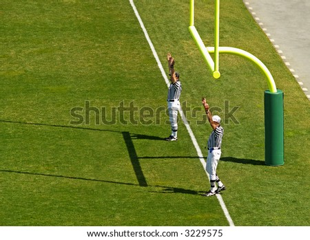 referees signaling a touchdown in football - stock photo