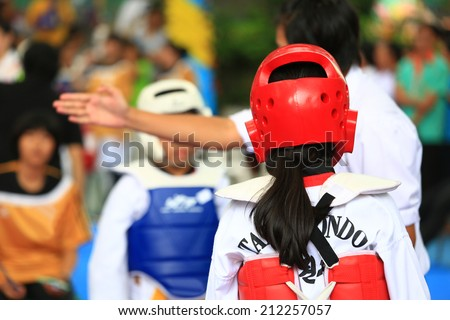 Referree gives signal to girls during Taekwondo fighting contest