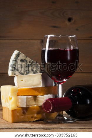Refined still life of wine and different types of cheesse on old wooden beige background