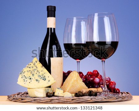 Refined still life of wine, cheese and grapes on wicker tray on wooden table on blue background - stock photo