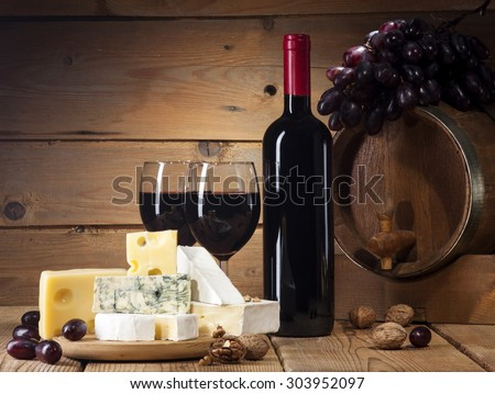 Refined still life of wine, cheese, walnuts, grapes and wooden barrel on old wooden beige background