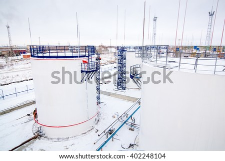 refinery factory oil storage tanks under cloudy sky - stock photo
