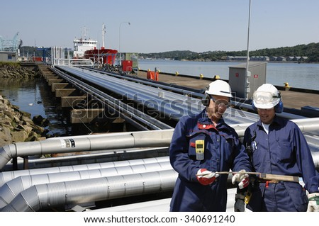 refinery pipelines leading to ships with two oil and gas workers - stock photo