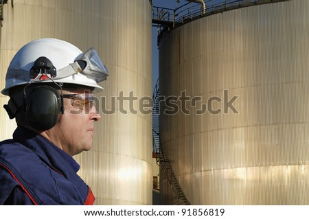 refinery worker, engineer inclose-ups, with large fuel-storage tanks in background - stock photo