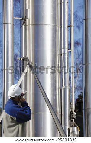 refinery worker pointing at large oil and gas pipes - stock photo