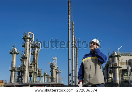refinery worker with chemical industry in background - stock photo
