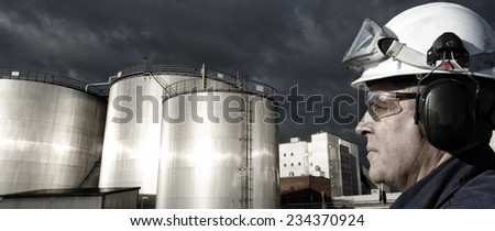 refinery worker with giant fuel storage tanks at sunset - stock photo