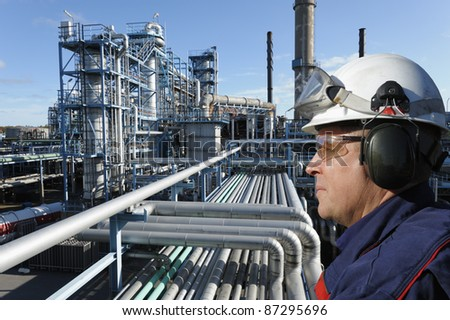 refinery worker with large petrochemical industry in background - stock photo