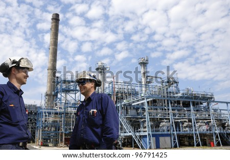 refinery workers and chemical plant in background