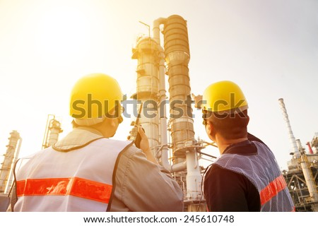 refinery workers discussion and pointing for inspection - stock photo