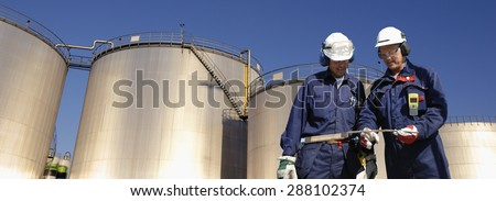 refinery workers, oil and fuel towers, panoramic view - stock photo
