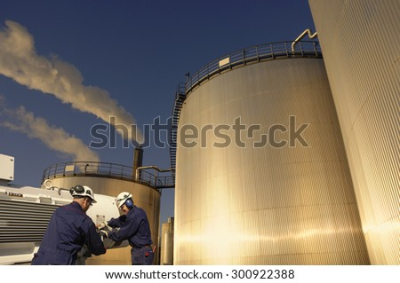 refinery workers with machinery and large fuel-storage tanks, towers, early evening sunset, focal point on workers - stock photo