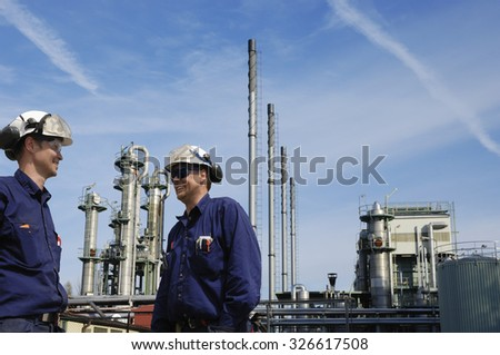 refinery workers with petro industry in the background - stock photo