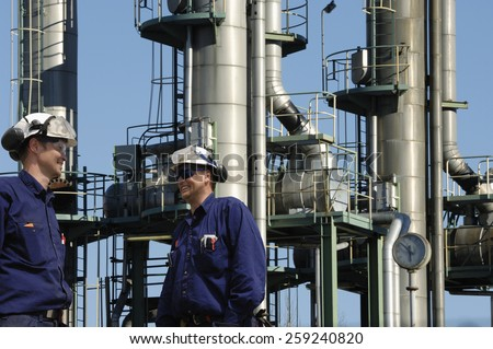refinery workers with three fuel towers inside industry, refinery detail - stock photo