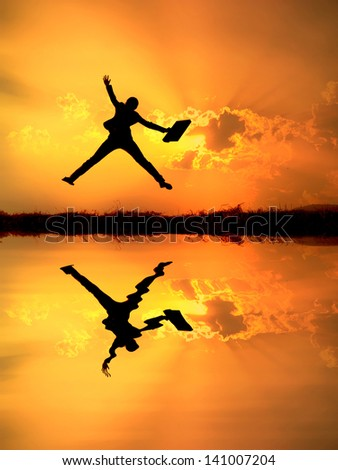 Reflect of Business woman jumping and sunset silhouette