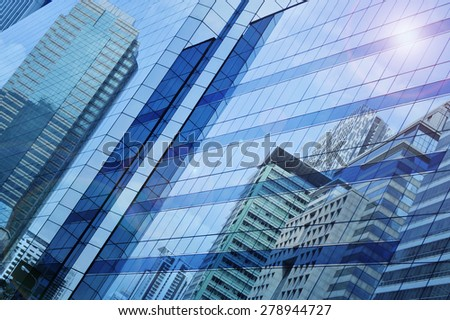Reflect of modern city building on window glass tower, blue tone, Bangkok Thailand