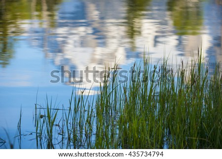 Reflected beautiful rugged rocky Teton snow capped mountain range blue sky majestic landscape scene in water  - stock photo