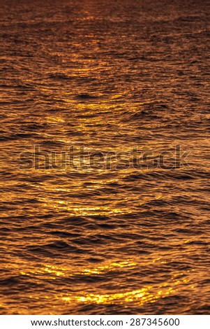 reflected warm yellow sunlight over the ocean water showing the texture of the sea - stock photo