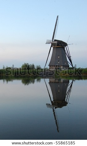 Reflected windmill in still water - stock photo