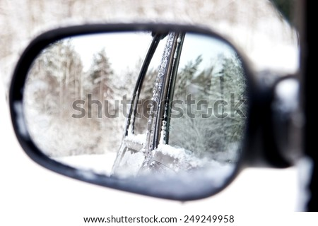 Reflecting of winter forest in a rear view car mirror - stock photo