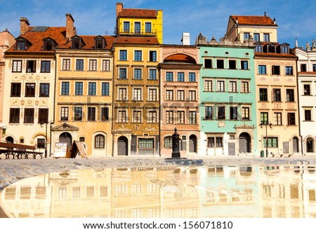 Reflecting surface of fountain and Warsaw, Poland old town marketplace square and colorful houses - stock photo
