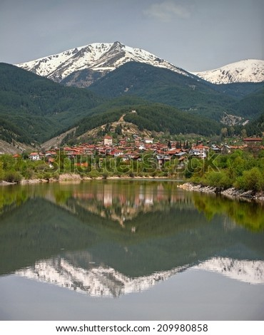 Reflection in a lake of a village and mountain behind - stock photo