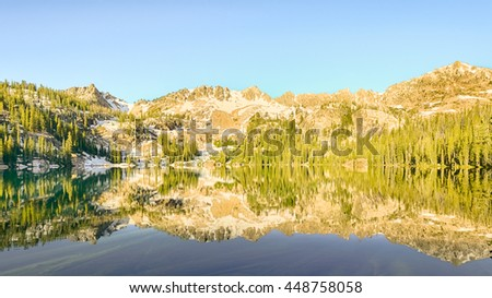 Reflection in Alpine Lake, in the Sawtooth National Recreation Area, near Stanley, Idaho. - stock photo