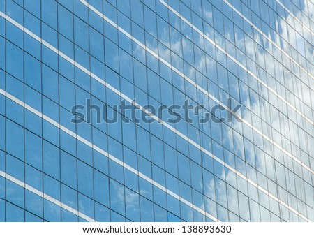 Reflection in glass wall of business building - stock photo
