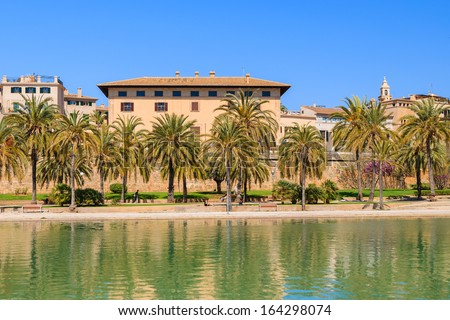 Reflection in lake of palace building near La Seu Cathedral  in Palma de Majorca with palm trees in front, Spain - stock photo