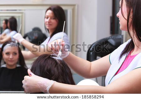 Reflection in mirror. Brunette woman in hairdressing beauty salon. Girl dyeing hair by hairstylist. hairdresser colouring client hair.