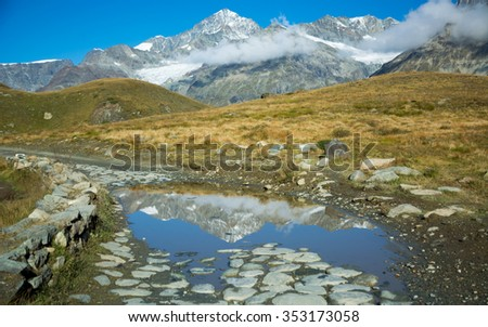 Reflection in the puddle, Alps, Schwarzsee - stock photo