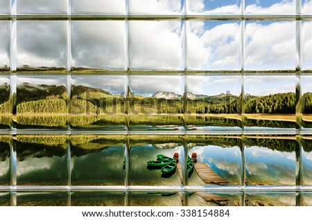 Reflection in water of mountain lakes and boats through window panes - stock photo