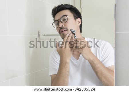 Reflection of a asian young man shaving in bathroom mirror - stock photo
