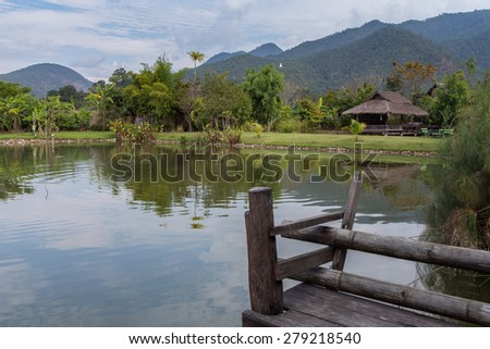 Reflection of a bamboo hut and mountain and trees on the water of a pond in rural Thailand. Serene with wooden dock in the foreground.