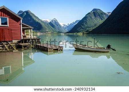 Reflection of a boat, a jetty, a red boathouse and some mountains in the still water of Fjaerlandsfjord, part of the Sognefjord in the village of Fjaerland or Mundal in Sogn og Fjordane, Fjord Norway. - stock photo