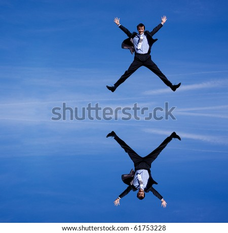 Reflection of a businessman jumping against blue skies