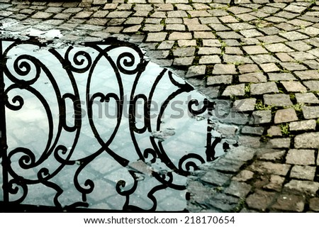 Reflection of a cast iron fence in a rain puddle. Abstract. High contrast, vintage processed.  - stock photo