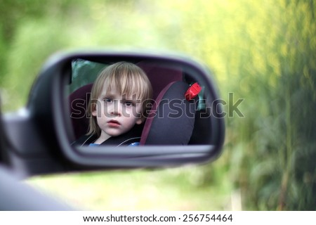 Reflection of a child in wing mirror - stock photo