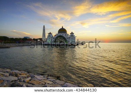 Reflection of a modern beautiful mosque during blue hour sunrise in Malacca, Malaysia. Noise slightly visible due to high iso and long exposure. - stock photo