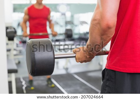 Reflection of a muscular man lifting barbell in gym