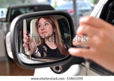 Reflection of a red head woman buying a new car - a series of BUYING A NEW CAR images. - stock photo
