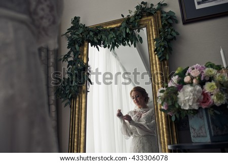 Reflection of a tender bride in dlicate lace dress in a mirror in golden frame - stock photo