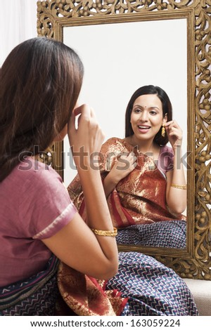 Reflection of a woman in mirror trying a sari and earring on herself
