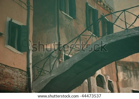 Reflection of an old bridge over a canal in Venice - stock photo