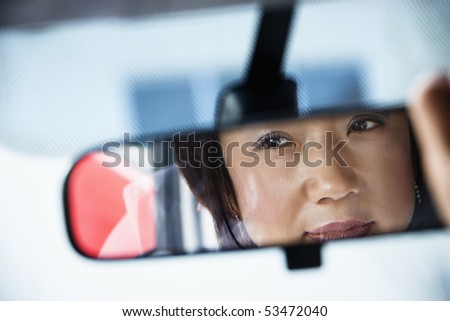 Reflection of Asian woman in rearview car mirror. - stock photo