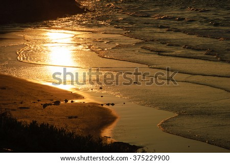 Reflection of beautiful golden sunset in the sea water.Peaceful serene landscape. Nature background. A game of light and shadow. - stock photo