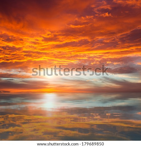 Reflection of Beautiful Sunset / Orange and Red Majestic Clouds above Water - stock photo